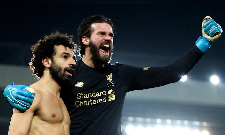 Mohamed Salah celebrates with Alisson after scoring Liverpool's second goal against Manchester United in January 2020 from the goalkeeper's pass.