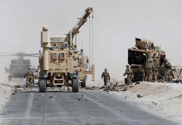 <p>U.S. troops assess the damage to an armoured vehicle of NATO-led military coalition after a suicide attack in Kandahar province, Afghanistan Aug. 2, 2017. (Photo: Ahmad Nadeem/Reuters) </p>