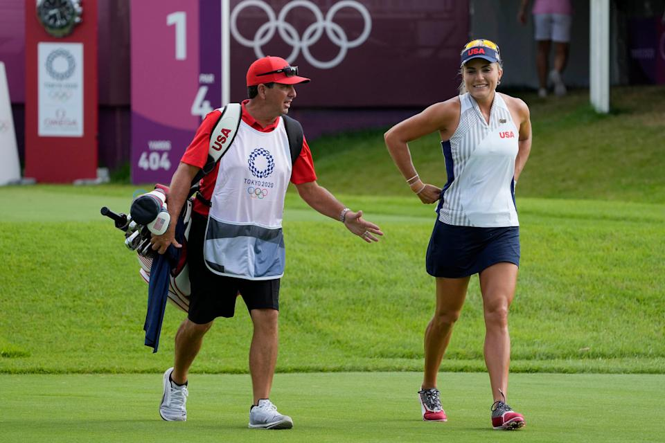 Lexi Thompson walks off the first tee box with her caddie during the first round of the women's individual stroke play at the Olympics.