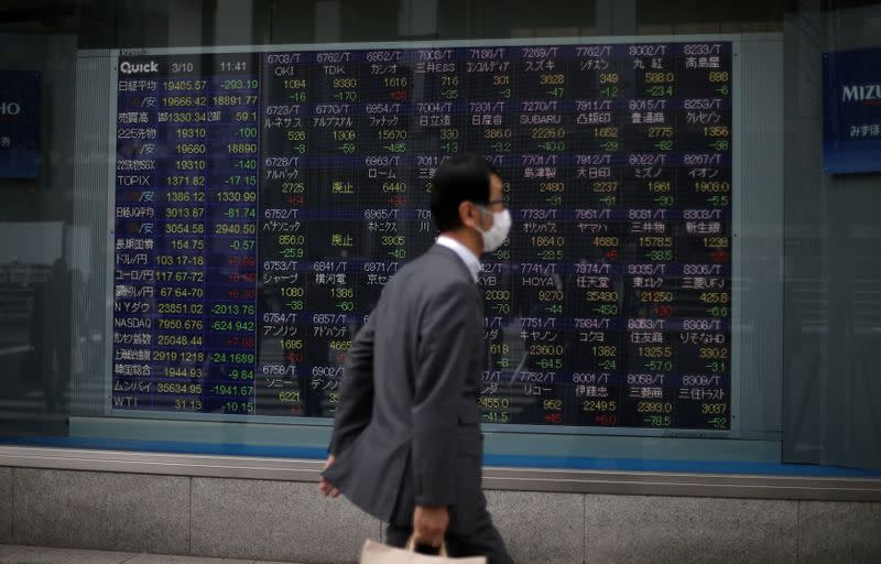 FILE PHOTO: A man wearing protective face mask walks in front of a stock quotation board outside a brokerage in Tokyo