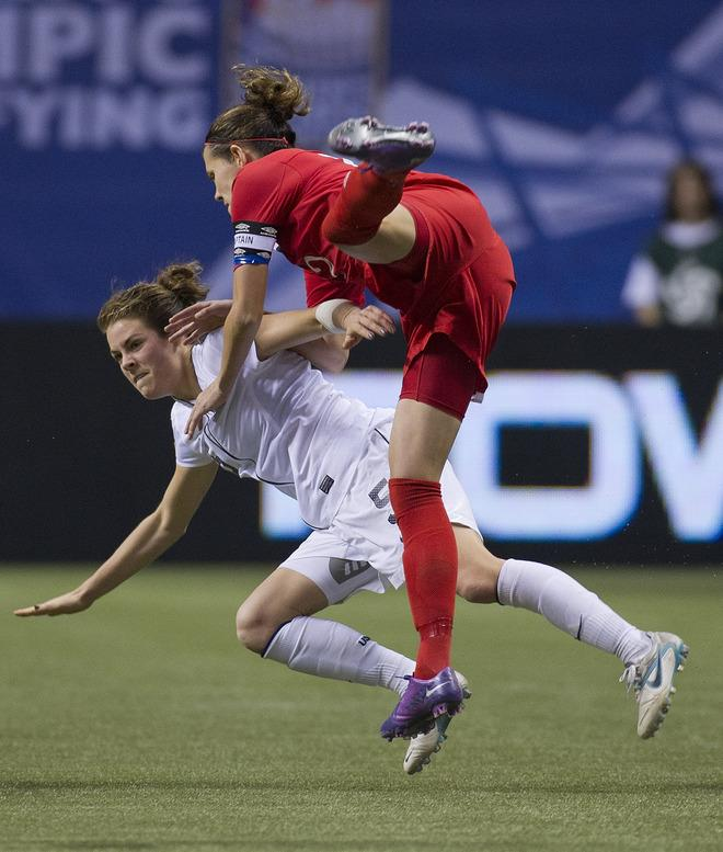 VANCOUVER, CANADA - JANUARY 29:  Christine Sinclair #12 of Canada collides with Kelley O'Hara #5 of the United States during second half of championship action of the 2012 CONCACAF Women's Olympic Qualifying Tournament at BC Place on January 29, 2012 in Vancouver, British Columbia, Canada.  (Photo by Rich Lam/Getty Images)