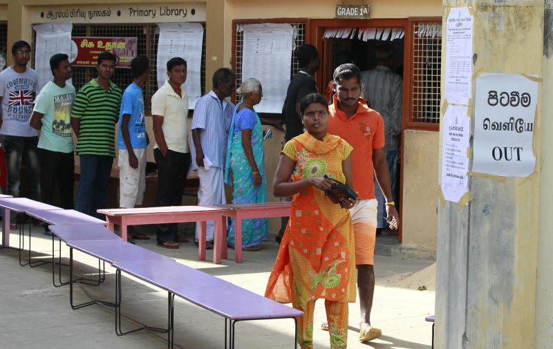 A Sri Lankan ethnic Tamil couple leaves after casting their vote as others line up to vote at a polling station during the northern provincial council election in Jaffna, Sri Lanka, Saturday, Sept. 21, 2013. The Tamils who are concentrated in the country's northern province are taking part in the election to form their first functioning provincial council, hoping that it will be first step toward winning wider self-government which they failed to achieve over the past 60 years, first through non-violent protests and strikes and later through a bloody quarter-century civil war.(AP Photo/Eranga Jayawardena)