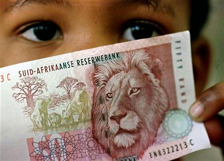 A South African child holds a 50 rand note July 2. The rand sank to a fresh low against the dollar i..