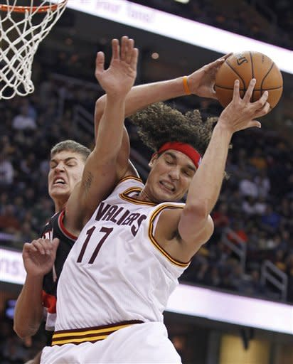 Cleveland Cavaliers' Anderson Varejao (17), from Brazil, grabs a rebound ahead of Portland Trail Blazers' Meyers Leonard (11) in the second quarter of an NBA basketball game Saturday, Dec. 1, 2012, in Cleveland. (AP Photo/Tony Dejak)