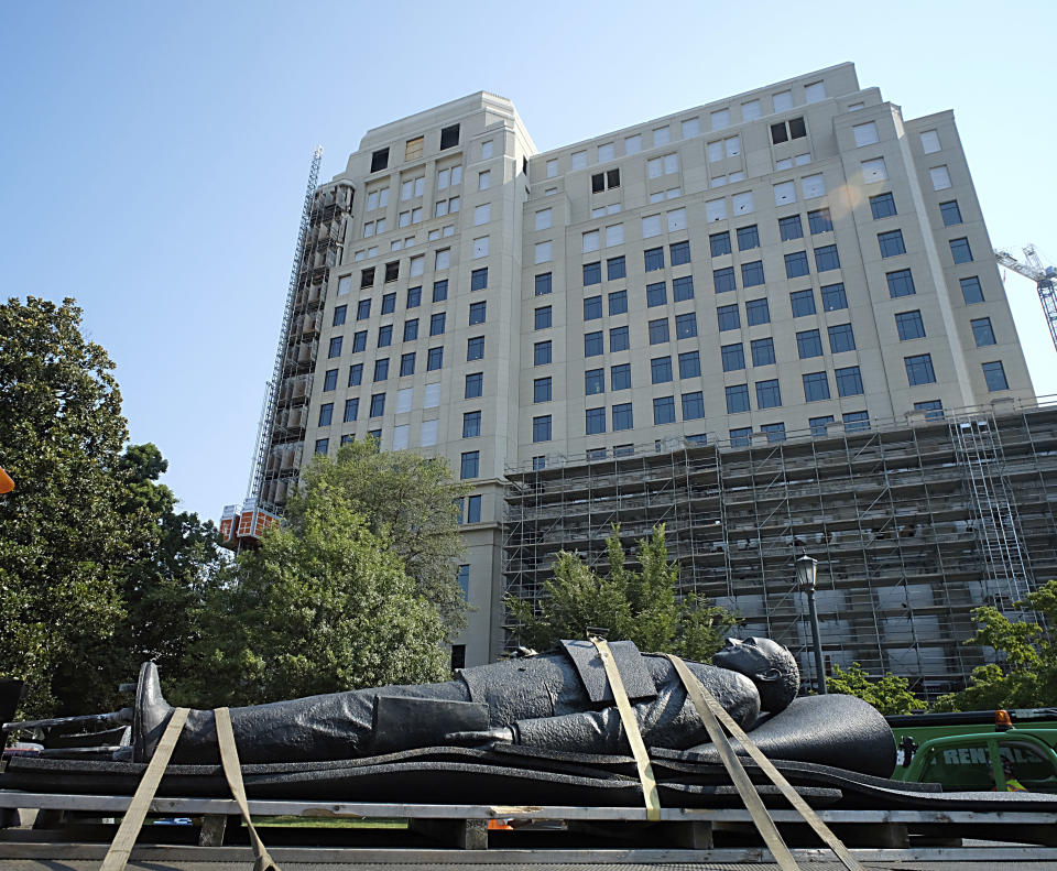 The statue of Harry F. Byrd, Sr., former Virginia Governor and U. S. Senator, lies on a flatbed truck in front of the new General Assembly Building under construction after it was removed from the pedestal in Capitol Square in Richmond, Va. Wednesday, July 7, 2021. The General Assembly approved the removal during the last session. (Bob Brown/Richmond Times-Dispatch via AP)