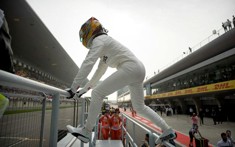 Lewis Hamilton goes to salute his fans - Credit: AP