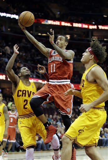 Milwaukee Bucks' Monta Ellis (11) goes in for a shot between Cleveland Cavaliers' Kyrie Irving (2) and Anderson Varejao in the first quarter of an NBA basketball game on Friday, Dec. 14, 2012, in Cleveland. (AP Photo/Mark Duncan)