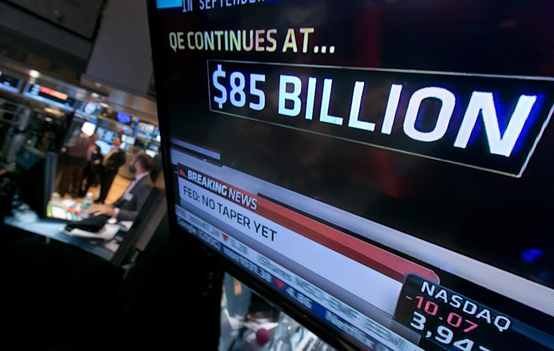 The decision of the Federal Reserve appears on a television screen on the floor of the New York Stock Exchange Wednesday, Oct. 30, 2013. The Fed says in a statement after a two-day policy meeting that it will keep buying $85 billion a month in bonds to keep long-term interest rates low and encourage more borrowing and spending. (AP Photo/Richard Drew)