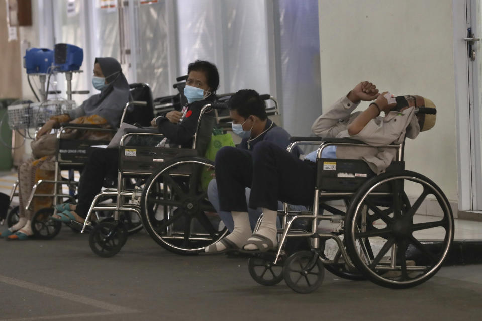 People wait for medical treatment outside an emergency ward amid a surge of COVID-19 patients at Cengkareng Regional General Hospital in Jakarta, Indonesia, Thursday, June 24, 2021. The world's fourth most populous country, has seen COVID-19 infections surge in recent weeks, putting pressure on hospitals, including in the capital city, where most of hospital beds are full, and has added urgency to the government's plan to inoculate 1 million people each day by next month. (AP Photo/Tatan Syuflana)