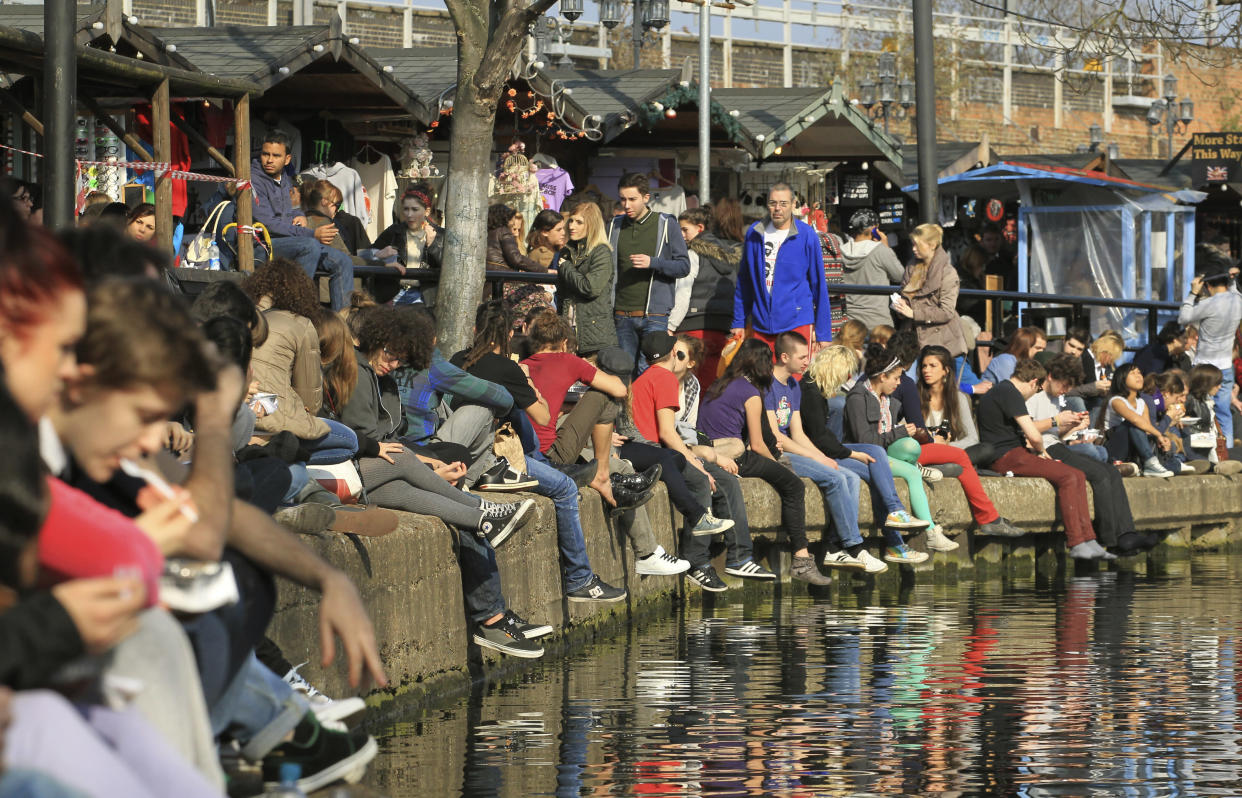 People sit in the sunshine along the canal in Camden, north London March 11, 2012. REUTERS/Olivia Harris (BRITAIN - Tags: SOCIETY)