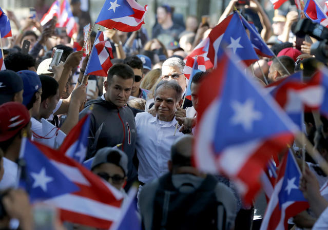 <p>Puerto Rican nationalist Oscar Lopez Rivera, center, arrives for a gathering in his honor in Chicago's Humboldt Park neighborhood, May 18, 2017. Lopez, who pardoned by former President Barack Obama in January, was freed from house arrest this week after decades in prison. The one-time leader in the Armed Forces of National Liberation, was honored with a parade and a street-way named after him as relatives of those killed in FALN bombings in the 1970s and '80s have criticized the moves to honor Lopez and cast him as a hero. (Photo: Charles Rex Arbogast/AP) </p>