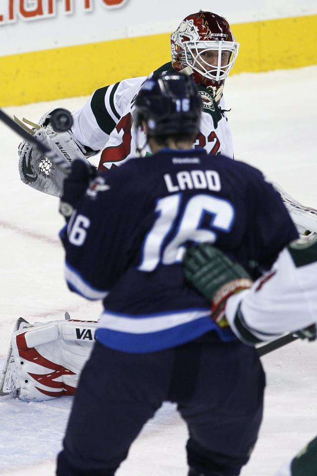 Minnesota Wild's goaltender Niklas Backstrom (32) watches the rebound as Winnipeg Jets' Andrew Ladd (16) attempts to knock it in during the first period of an NHL game in Winnipeg, Manitoba, Saturday, Nov. 23, 2013. (AP Photo/The Canadian Press, John Woods)