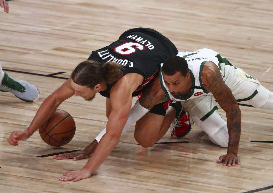 Miami Heat forward Kelly Olynyk (9) and Milwaukee Bucks guard George Hill (3) play for the ball during the second half of an NBA basketball game Thursday, Aug. 6, 2020, in Lake Buena Vista, Fla. (Kim Klement/Pool Photo via AP)
