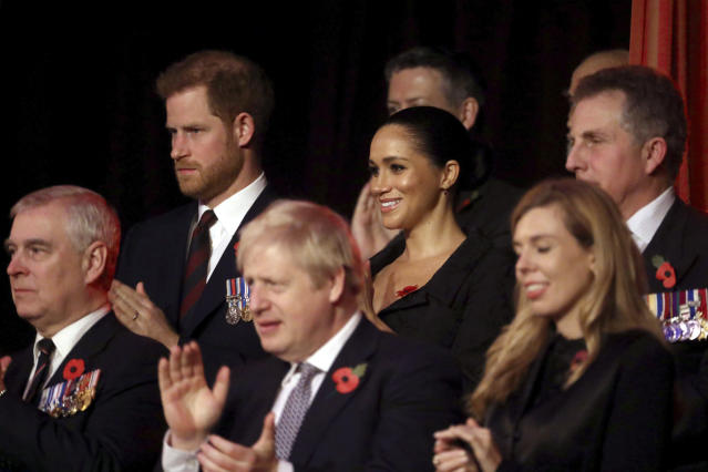 Britain's Prince Harry, background left and Meghan, the Duchess of Sussex attend the annual Royal British Legion Festival of Remembrance, at the Royal Albert Hall in Kensington, London, Saturday, Nov. 9, 2019. In the front row is Prince Andrew, Britain's Prime Minister Boris Johnson and Carrie Symonds. (Chris Jackson/Pool Photo via AP)