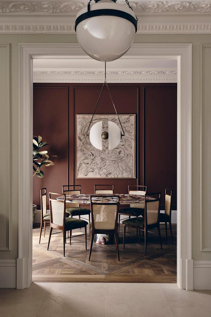 Swathed in Paint & Paper Library's sultry Masai, the dining room is complete with a Dirk van der Kooij dining table surrounded by elegant chairs that were handmade in Brazil.