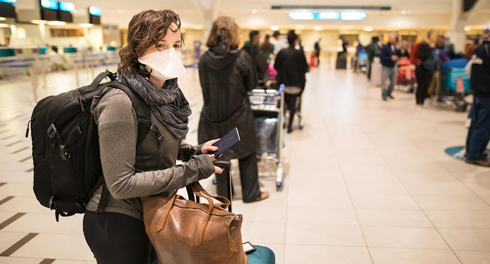 Woman waiting in a long line for a flight wearing a N95 face mask during a global pandemic