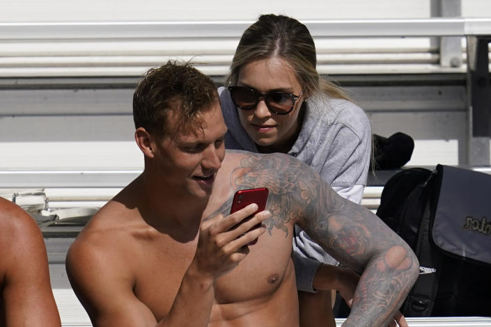 FILE - In this April 10, 2021, file photo, Caeleb Dressel, left, and his wife, Meghan Dressel, look at a phone in the stands before the TYR Pro Swim Series swim meet in Mission Viejo, Calif. For a man tabbed as swimming's next superstar, Dressel could not be more disinterested. Of course, he cares about being fast in the pool. He just is not into anyone else's expectations or comparisons. Fame is not his thing, either. (AP Photo/Ashley Landis, File)