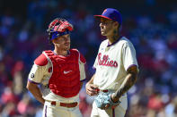 Philadelphia Phillies' J.T. Realmuto, left, talks to staring pitcher Hans Crouse during the third inning of a baseball game against the Pittsburgh Pirates, Sunday, Sept. 26, 2021, in Philadelphia. (AP Photo/Derik Hamilton)