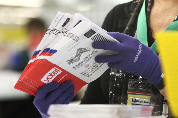 An election worker sorts vote-by-mail ballots in Renton, Wash., on March 10. (Jason Redmond/AFP via Getty Images)