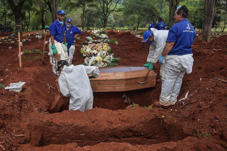 Employees bury a person who died suspectedly from COVID-19 at the Vila Formosa cemetery, in the outskirts of Sao Paulo, Brazil on March 31, 2020. - Vila Formosa cemetery, the largest in Latin America with an area of 780 thousand square meters and where more than 1.5 million people were buried, had a 30% increase in the number of burials after the beginning of the COVID-19 pandemic. (Photo by NELSON ALMEIDA / AFP) (Photo by NELSON ALMEIDA/AFP via Getty Images)