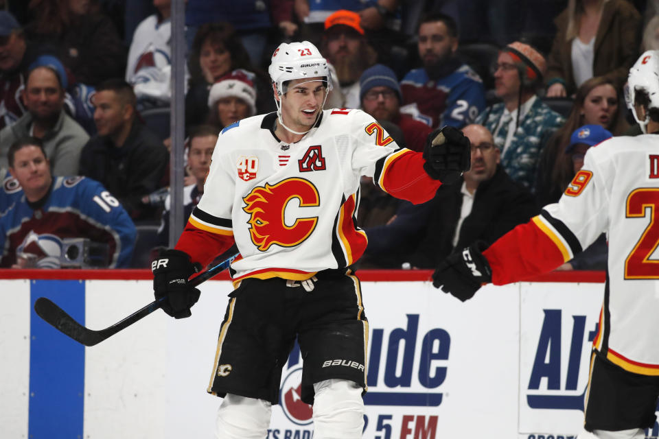 Calgary Flames center Sean Monahan, left, celebrates scoring the winning goal with center Dillon Dube in overtime of an NHL hockey game against the Colorado Avalanche Monday, Dec. 9, 2019, in Denver. The Flames won 5-4 in overtime. (AP Photo/David Zalubowski)