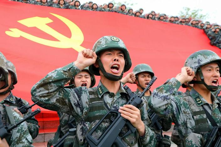"""Soldiers seen in front of the flag of the Communist Party of China at an official event on April 13, 2021 in Luoyang, Henan Province, China.<span class=""""copyright"""">Jia Fangwen/VCG via Getty Images</span>"""