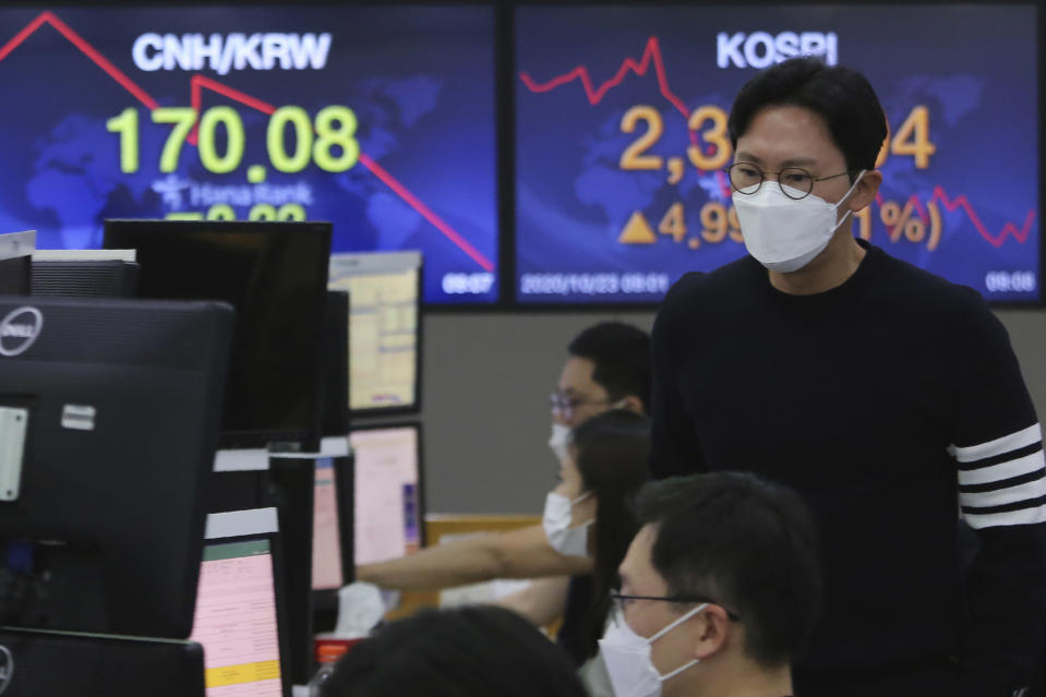 A currency trader watches monitors at the foreign exchange dealing room of the KEB Hana Bank headquarters in Seoul, South Korea, Friday, Oct. 23, 2020. Shares were mostly higher in Asia on Friday after President Donald Trump and his challenger former Vice President Joe Biden faced off in their second and final debate before the Nov. 3 election. (AP Photo/Ahn Young-joon)