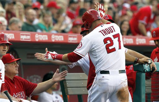 Los Angeles Angels' Mike Trout (27) is congratulated by manager Mike Scioscia, left, and teammates after scoring from third on a sacrifice fly in the first inning against the Oakland Athletics during a baseball game on Saturday, July 20, 2013, in Anaheim, Calif. (AP Photo/Alex Gallardo)