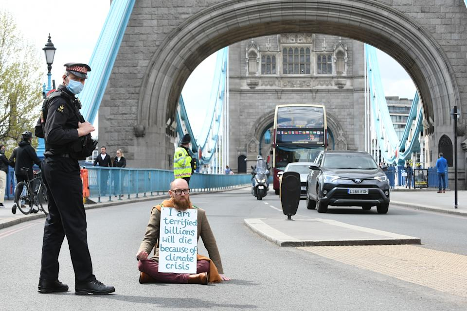 Extinction Rebellion (XR) handout photo of Morgan Trowland, 38, blocking traffic on Tower Bridge in London, as hundreds of people are staging