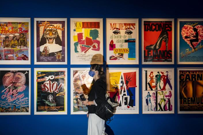 A person wearing a mask walks past a wall covered in posters