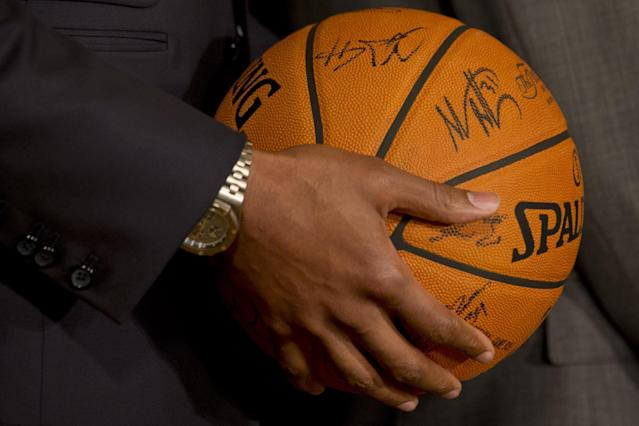 Miami Heat basketball player Chris Bosh holds a signed basketball for President Barack Obama during an event in the East Room of the White House in Washington, Tuesday, Jan. 14, 2014, where the president honored the 2013 NBA Champion basketball team. (AP Photo/Jacquelyn Martin)