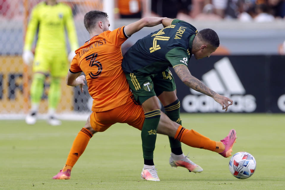 Houston Dynamo defender Adam Lundqvist (3) kicks through the block by Portland Timbers midfielder Marvin Loria (44) during the first half of an MLS soccer match Wednesday, June 23, 2021, in Houston. (AP Photo/Michael Wyke)
