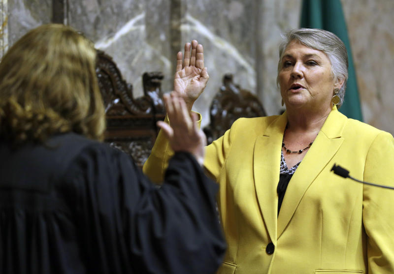 FILE - In this Jan. 9, 2017 file photo, Sen. Maureen Walsh, R-Walla Walla, right, takes the oath of office on the opening day of the 2017 legislative session at the Capitol in Olympia, Wash. Walsh opposes a measure that has Washington poised to become the first state to establish an employee-paid program creating an insurance benefit to help offset the costs of long-term care, saying that people do need long-term care insurance, but that the state should incentivize existing private-sector programs. The measure is facing a final vote in the House. (AP Photo/Ted S. Warren, File)