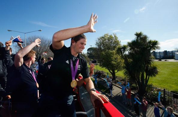 Gold medalist Nathan Cohen waves to school children as they travel by bus to the New Zealand Olympic homecoming ceremony at Pioneer Stadium on August 24, 2012 in Christchurch, New Zealand. (Photo by Sandra Mu/Getty Images)