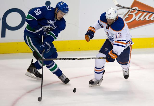 Vancouver Canucks' Brendan Gaunce, left, and Edmonton Oilers' Mike Brown compete for a loose puck during the second period of a preseason NHL hockey game Wednesday, Sept. 18, 2013, in Vancouver, British Columbia. (AP Photo/The Canadian Press, Darry Dyck)