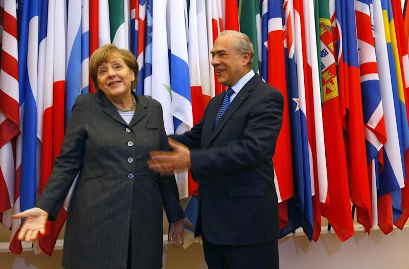 Head of the Organization for Economic Co-operation and Development (OECD) Angel Gurria, centre, and Germany's Chancellor Angela Merkel, react, prior to their meeting at the OECD headquarters in Paris, Wednesday, Feb. 19, 2014. (AP Photo/Michel Spingler)