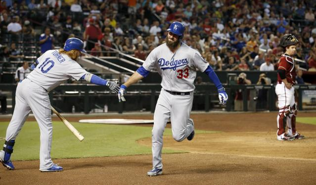 Los Angeles Dodgers' Scott Van Slyke (33) shakes hands with teammate Justin Turner (10) after Van Slyke's home run as Arizona Diamondbacks' Tuffy Gosewisch, right, looks on during the third inning of a baseball game Wednesday, Aug. 27, 2014, in Phoenix. (AP Photo/Ross D. Franklin)