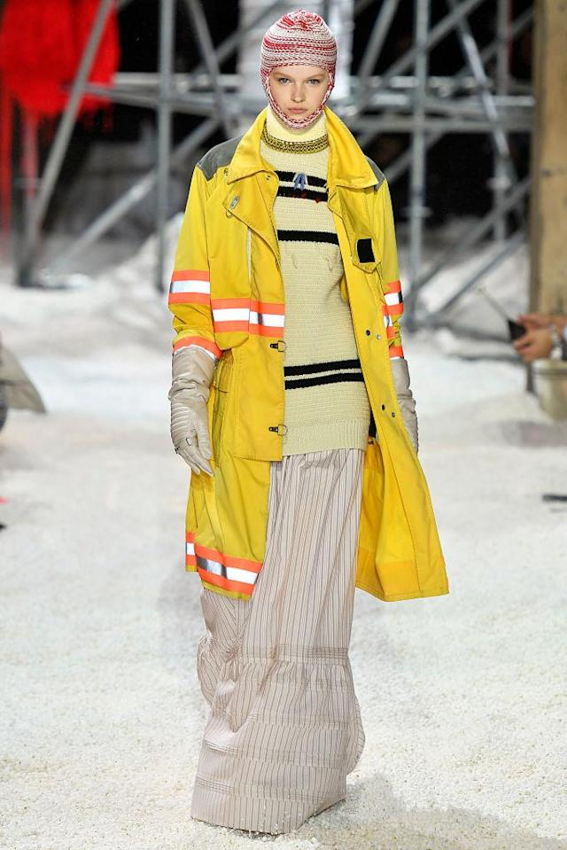 <p>A model wears a yellow safety coat with orange reflective paneling, a balaclava, a striped sweater, gloves, and a prairie skirt at the Calvin Klein fall 2018 show. (Photo: Getty Images) </p>
