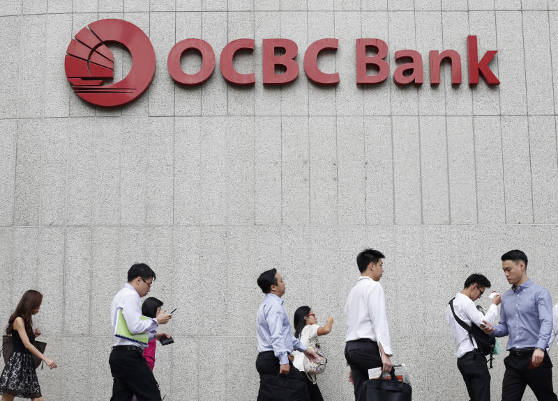 Office workers walk past an OCBC branch in Singapore's financial district. (Reuters file photo)
