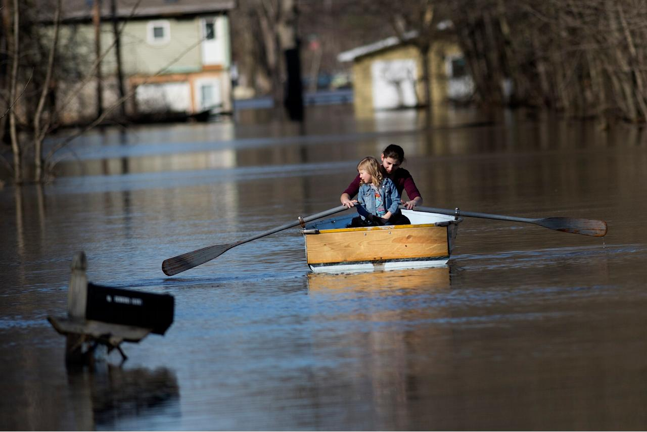 <p>Emily Snyder teachers her daughter, Skyler, 4, how to row the boat as they check out their home on Forrest Ridge Avenue NE in Plainfield Township, Mich., on Monday, Feb. 26, 2018. River levels are dropping in Michigan after flooding last week and over the weekend because of heavy rains and melting snow. The National Weather Service says the Grand River in Grand Rapids crested Sunday above 20 feet (6 meters), more than 2 feet (0.7 meters) higher than flood stage, after peaking Friday in the Lansing area. Still, local states of emergency were in effect Monday along portions of the river. (Photo: Neil Blake/The Grand Rapids Press via AP) </p>