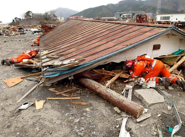 British search and rescue workers search under a roof removed from a house for survivors of the tsunami in Ofunato, Japan, Tuesday, March 15, 2011.  Two search and rescue teams from the U.S. and a team from the U.K. with combined numbers of around 220 personnel, searched damaged areas of the town of Ofunato for trapped survivors Tuesday in the aftermath of the earthquake and tsunami. (AP Photo/Matt Dunham)