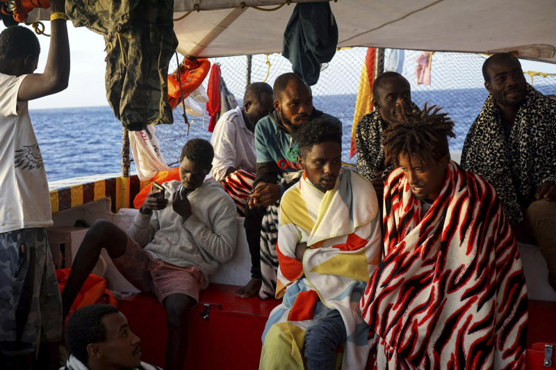 Migrants sit aboard the Open Arms Spanish humanitarian boat as it arrives near Lampedusa coast in the Mediterranean Sea, Thursday, Aug.15, 2019. A Spanish aid boat with 147 rescued migrants aboard is anchored off a southern Italian island as Italy's ministers spar over their fate. (AP Photo/Francisco Gentico)
