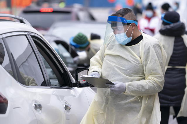 A health-care worker screens people in their vehicle at a COVID-19 test clinic in Montreal on Monday, March 23, 2020. (Paul Chiasson/The Canadian Press via AP)