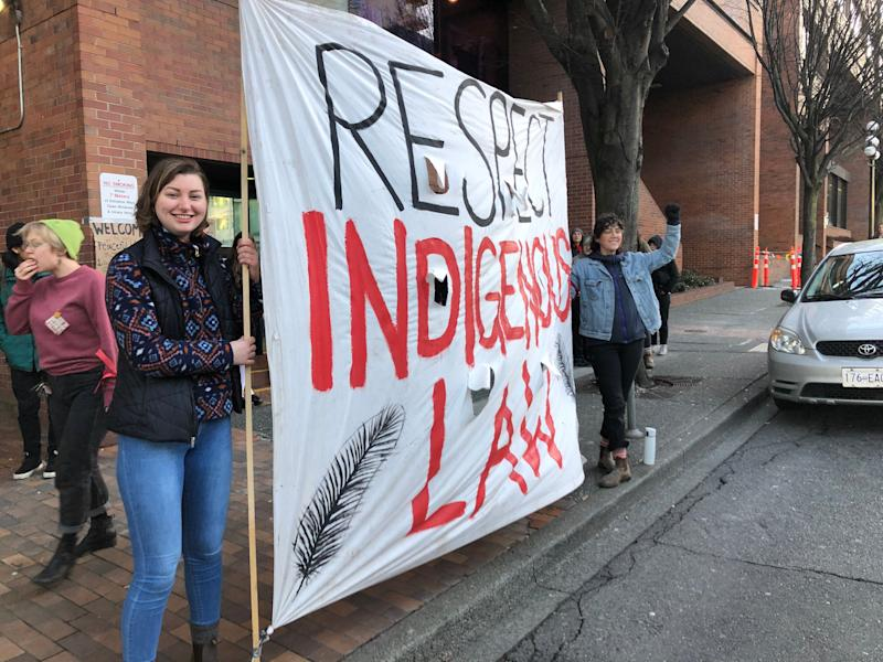 "Allies of the Wet'suwet'en hereditary chiefs stand with a sign reading ""Respect Indigenous Law"" outside a B.C. provincial ministry building in Victoria on Feb. 14, 2020. (Photo: Melanie Woods/HuffPost Canada)"