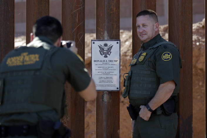 FILE - In this Oct. 26, 2018, file photo, Border Patrol agent Michael Sullivan, right, poses for a picture next to a plaque adorning a newly fortified border wall structure in Calexico, Calif. President Donald Trump is visiting Calexico on Friday, April 5, 2019, to tour a recently-built portion of the border fence that bears the silver plaque with his name on it. (AP Photo/Gregory Bull, File)