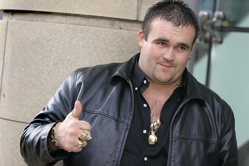 British Lottery winner Michael Carroll, covered in gold jewellery, gives a thumbs up to the camera.