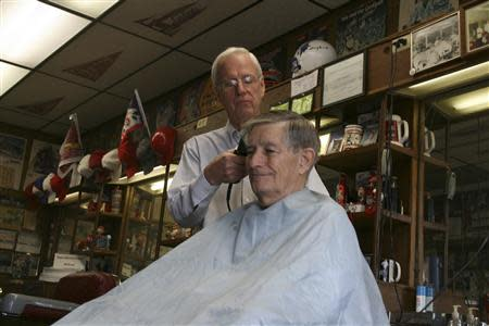 Rogers, Arkansas city council member Gary Townzen (L) cuts the hair of Ray Sanford in his barbershop in Rogers December 4, 2013. REUTERS/Andy Sullivan