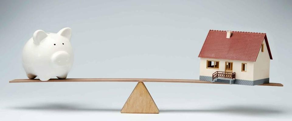 Home loan market.  Model house and piggy bank balanced on a swing