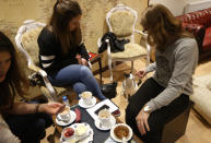 "Visitors feed a cat in the newly opened Lady Dinah's Cat Emporium in London, Friday, April 4, 2014. Feline company is exactly what one of London's newest cafes is offering _ and stressed-out city-dwellers are lapping it up. ""People do want to have pets and in tiny flats, you can't,"" said cafe owner Lauren Pears, who opened Lady Dinah's Cat Emporium last month in an area east of the city's financial district. (AP Photo/Sang Tan)"
