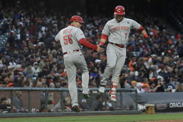 Cincinnati Reds' Eugenio Suarez, right, is congratulated by third base coach J.R. House (56) after hitting a solo home run against the San Francisco Giants during the fifth inning of a baseball game in San Francisco, Saturday, May 11, 2019. (AP Photo/Jeff Chiu)